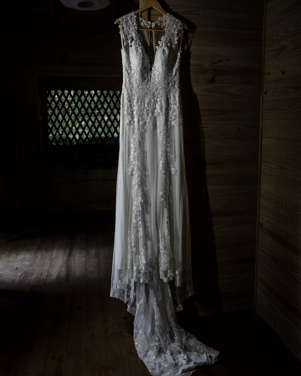Wedding dress hangs from wall in rustic bridal suite.