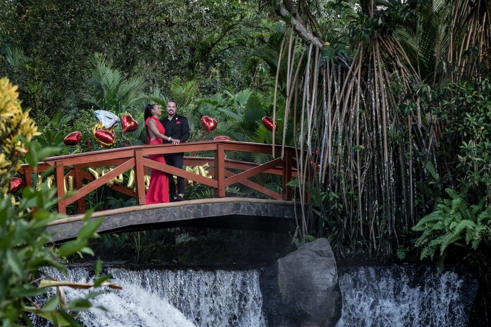 Couple on dreamy red bridge at Tabacon Resort gets engaged.