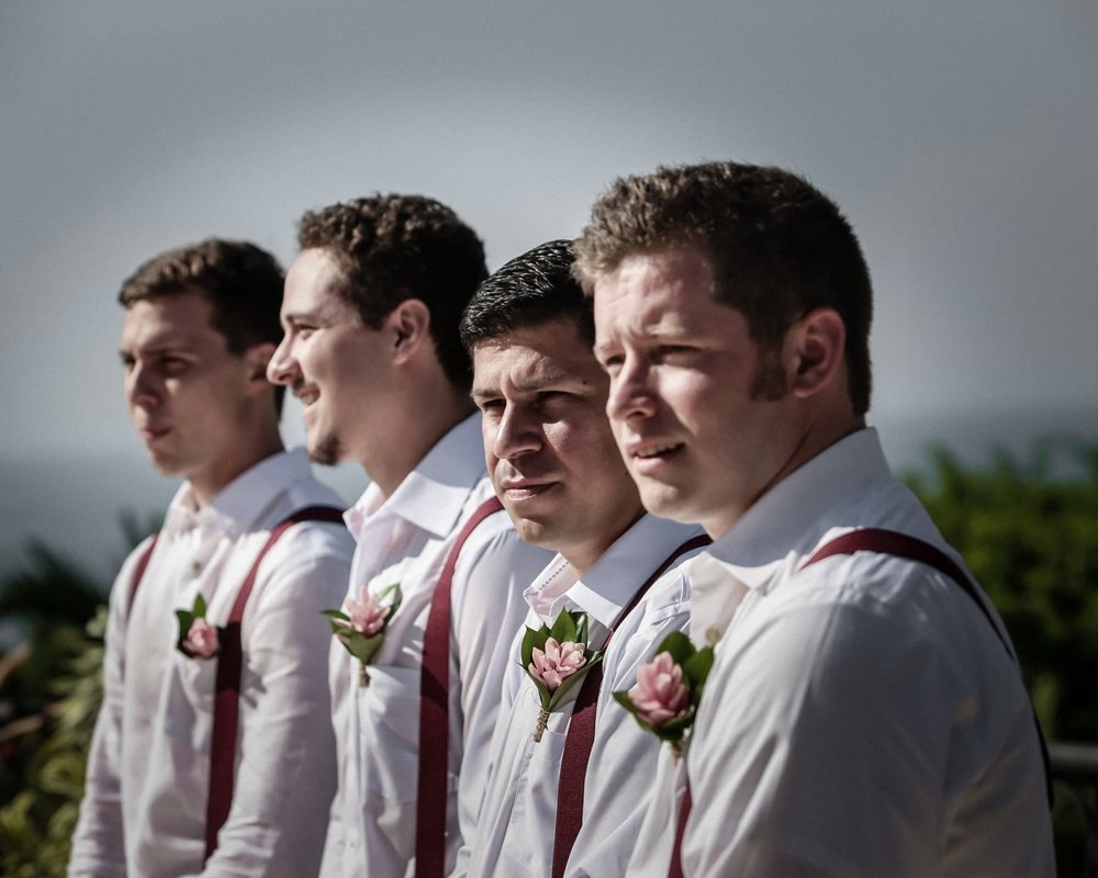 Groomsmen wearing exotic boutonnieres watch as couple gets married in Costa Rica.