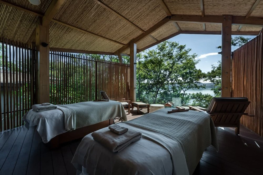 Bride and groom massage tables in private bungalow with unforgettable views.