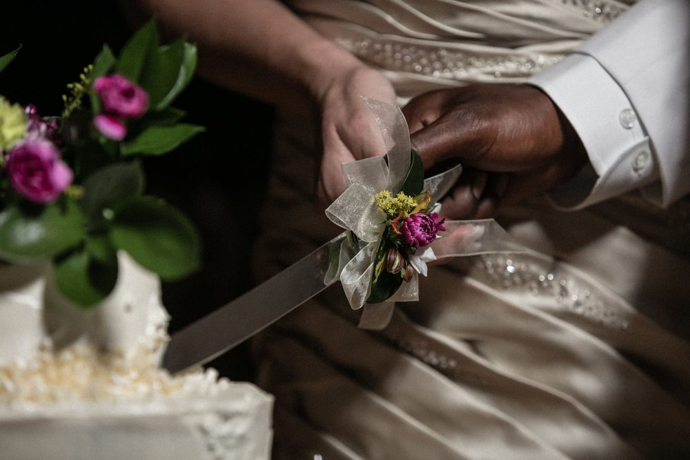 Couple cuts wedding cake together in honeymoon suite in Costa Rica.