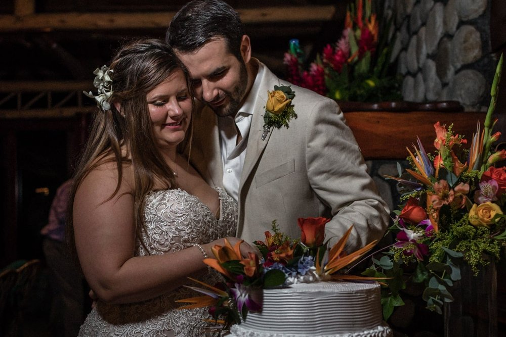 Bride and groom cut their wedding cake decorated with tropical flowers.