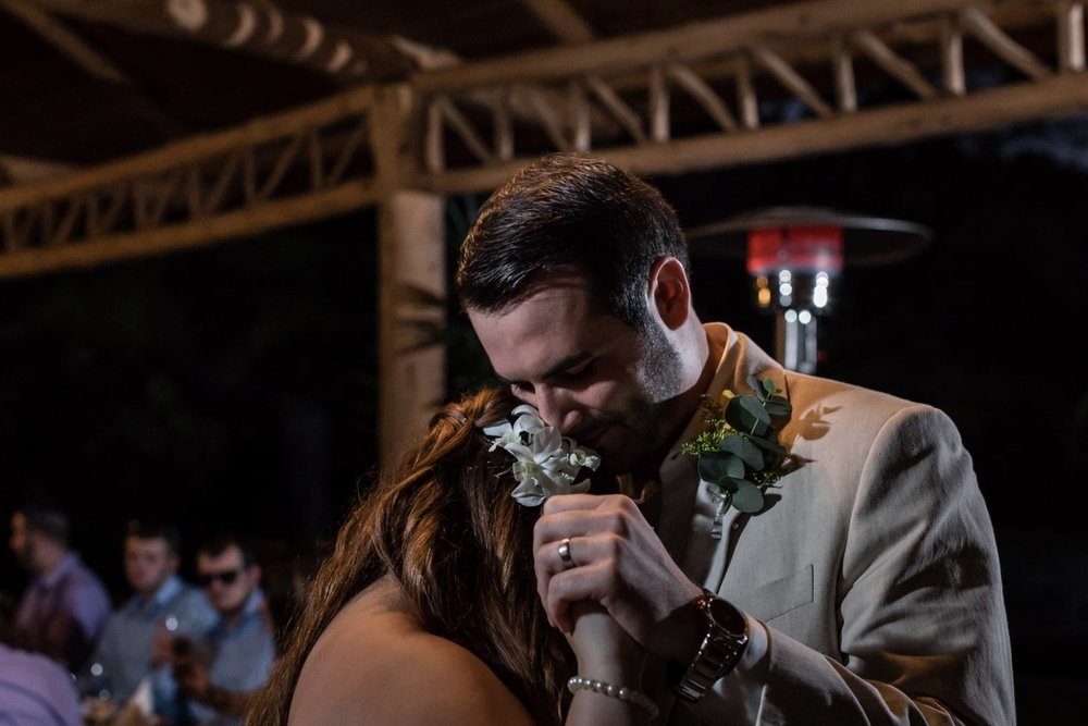 Moving photo of bride and groom during first dance at wedding reception.