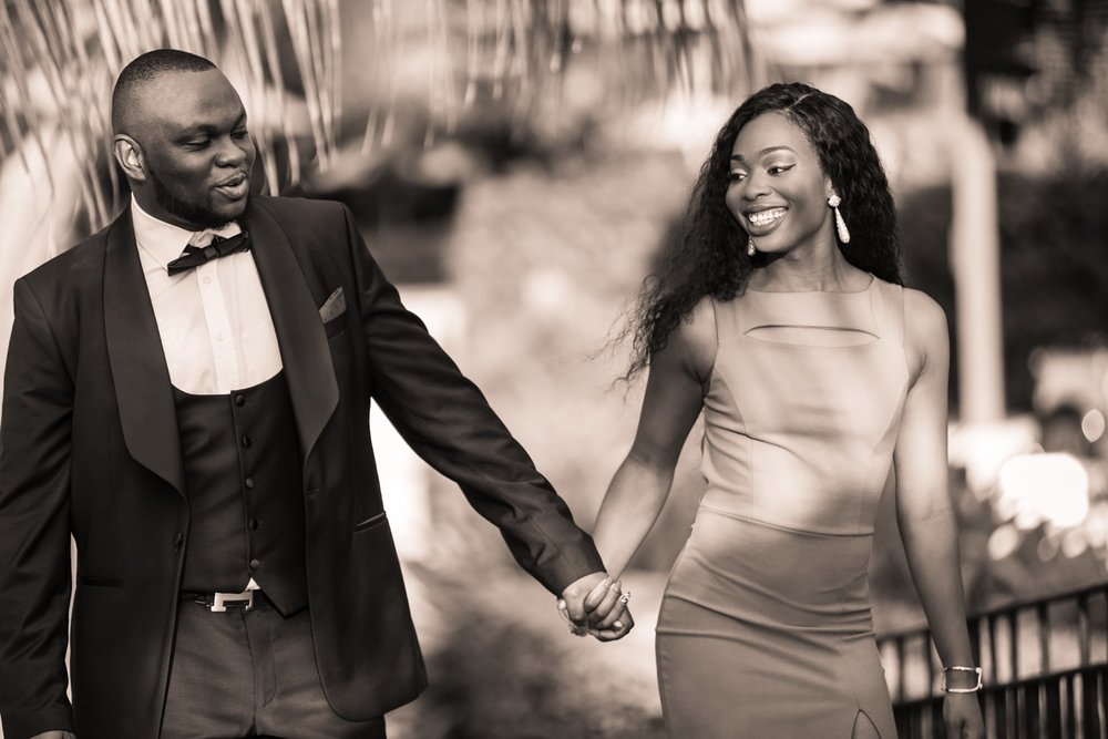 Happy couple holding hands and smiling after he proposed marriage.