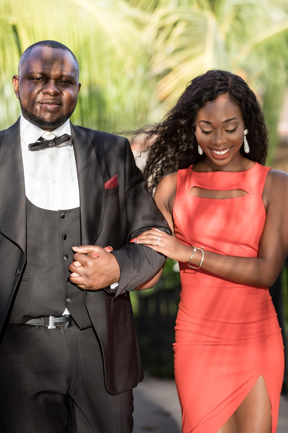 Just engaged couple walking arm in arm and smiling.