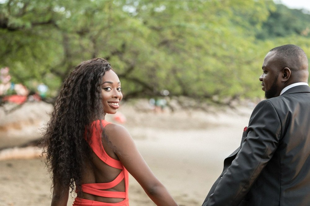 Fiancée looks at camera while walking on beach in Costa Rica after her love proposed marriage.