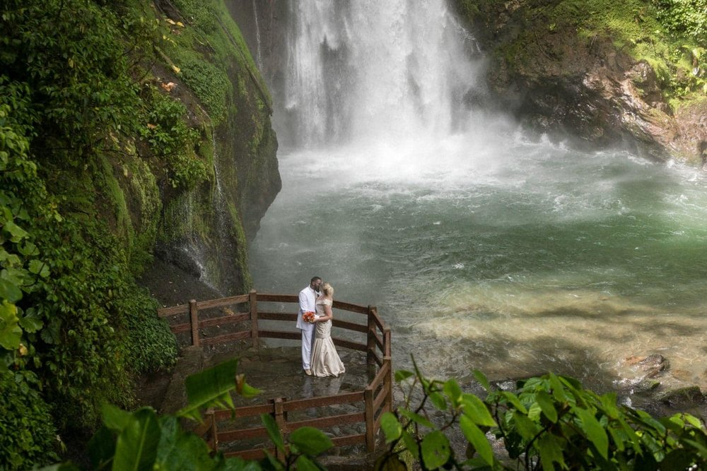 Wedding photo of couple in front of waterfall in Costa Rica.
