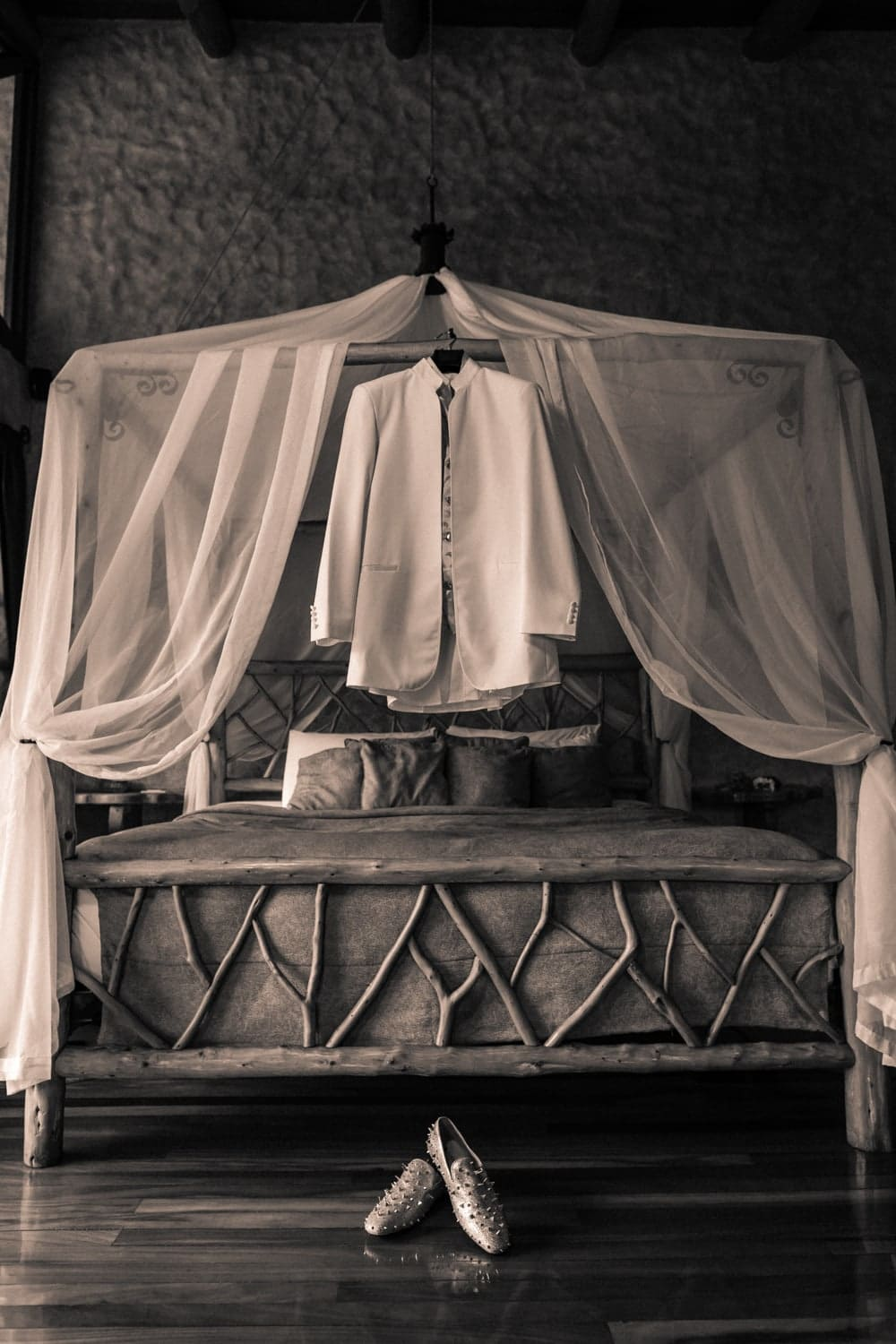 Grooms wedding day attire hanging on canopy bed.