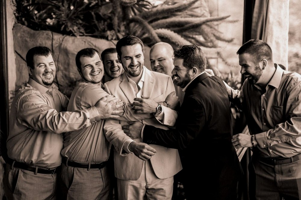 Groom and groomsmen on balcony in cloud forest resort before ceremony.