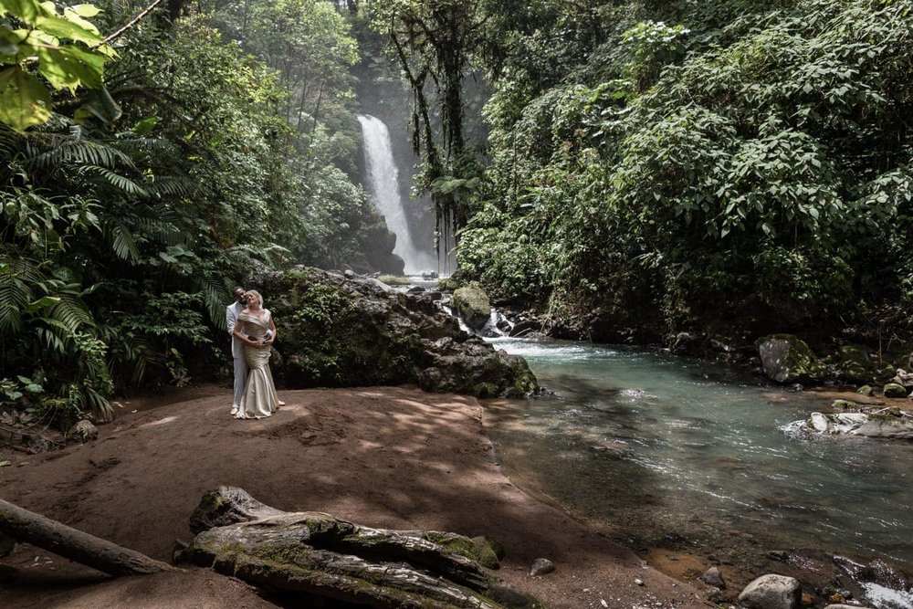 Just married couple pose for photo in front of breathtaking waterfall in Costa Rica.