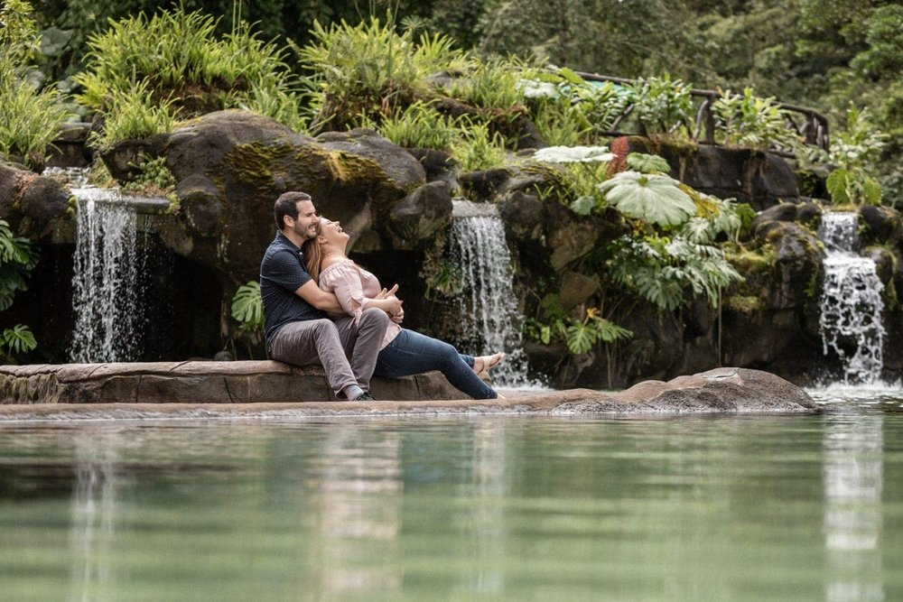 Lovers sitting on deck near pool with waterfalls in Costa Rica.