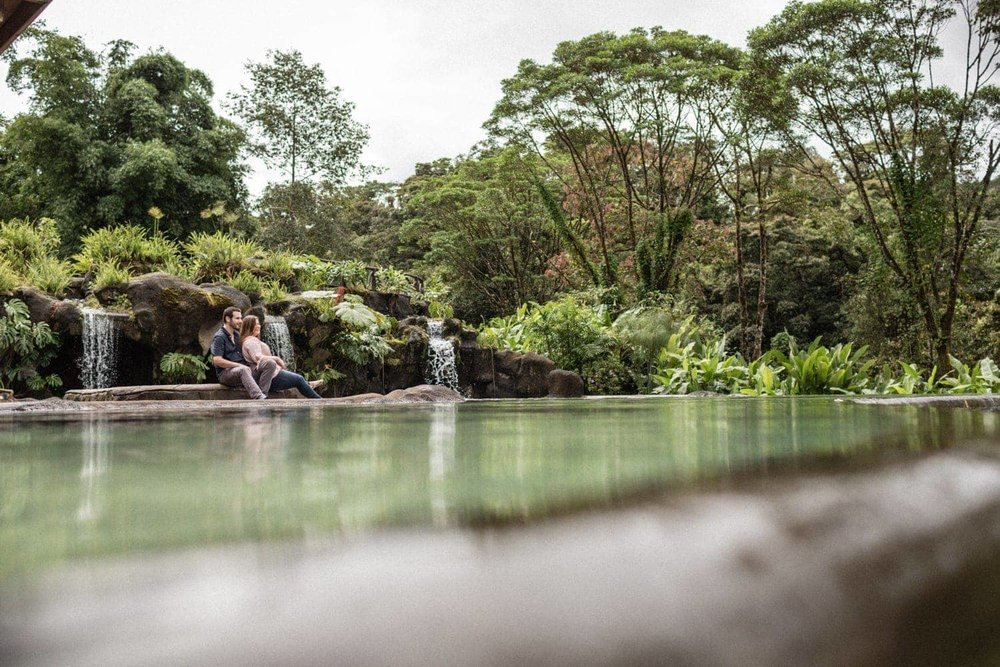 Engagement photo of couple by waterfall pool in rainforest.