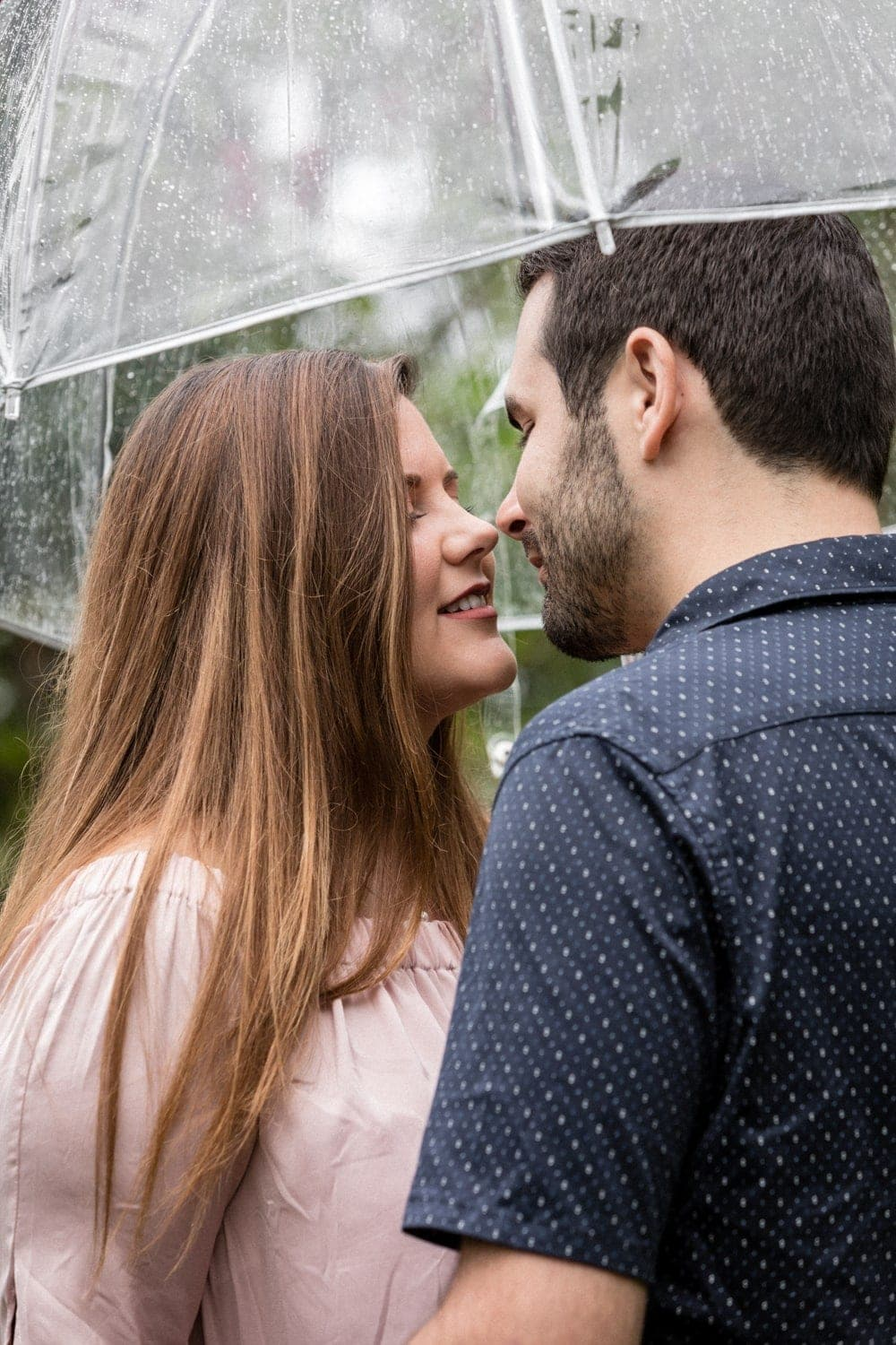 Couple share intimate moment under umbrella at La Paz Waterfall Gardens.