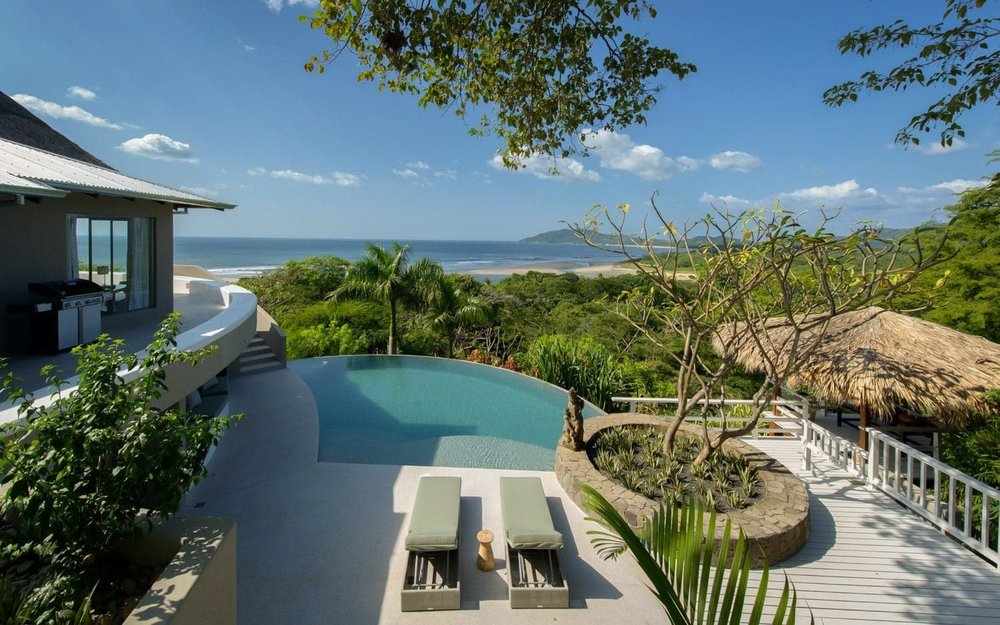 Upper view of pool with great beach and ocean views at Sunset House.
