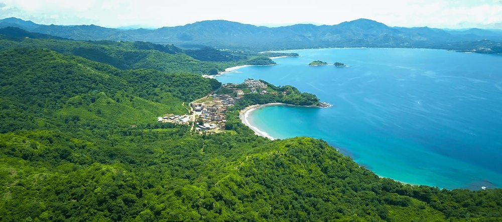 Arial view of the town of Las Catalinas surrounded by rainforest next to gorgeous Pacific-Coast beaches.