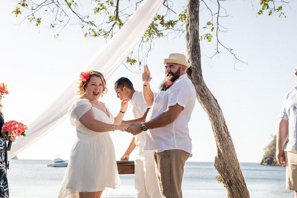 Couple getting married on beac in Costa Rica at sunset.