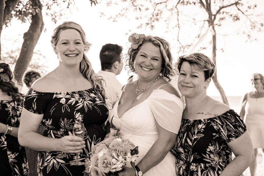 Black and white photo of bridesmaids after champaign toast on beach.