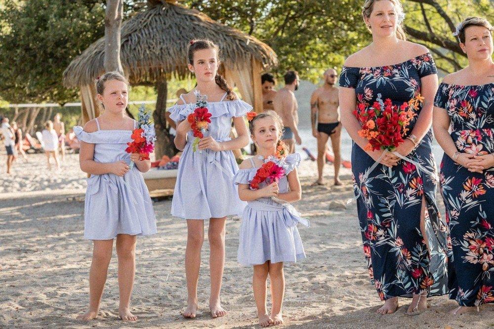 Bridesmaids holding bouquets during wedding ceremony at Dreams Las Mareas.