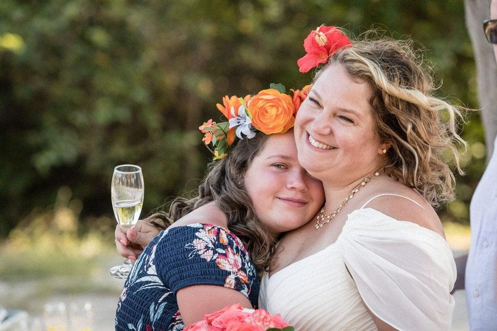 Bridesmaid hugs mother after wedding ceremony at Dreams Las Mareas.
