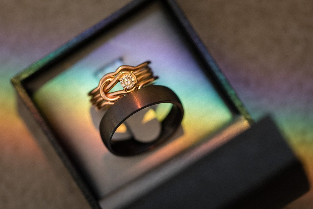 Bride and groom wedding bands with a rainbow running through them.