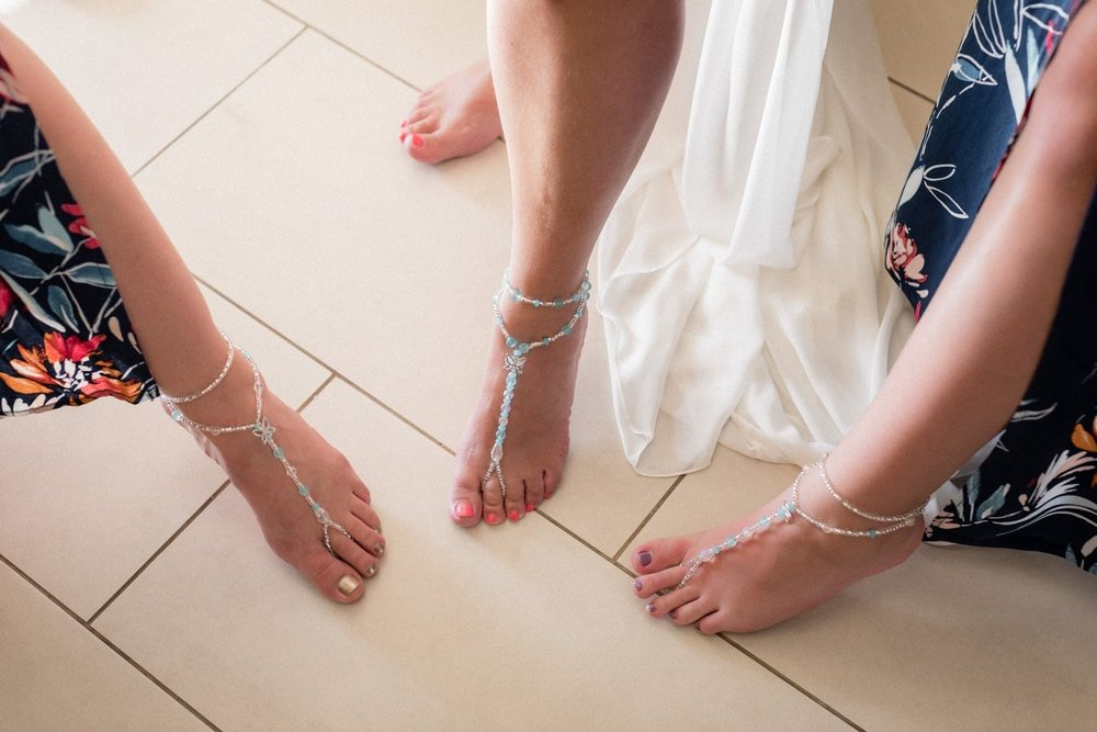 Bride and bridesmaids show their feet after preparing for wedding.