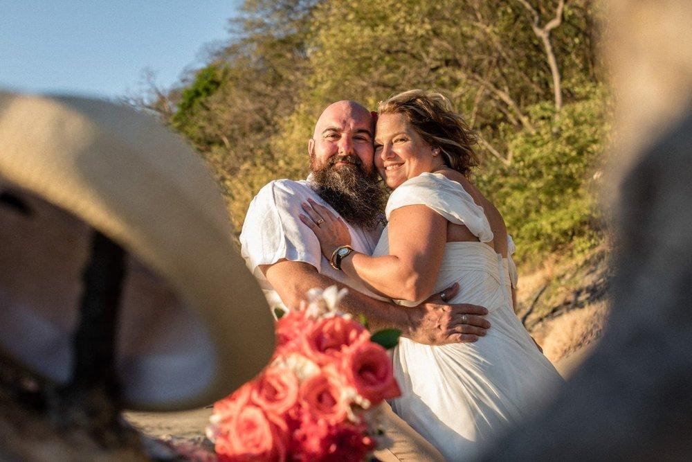 Bride and groom hug for wedding photo on beach.
