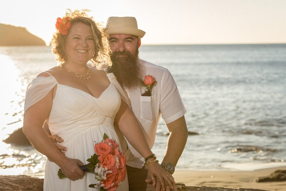 Bride and groom pose for portrait on beach in Costa Rica at sunset.