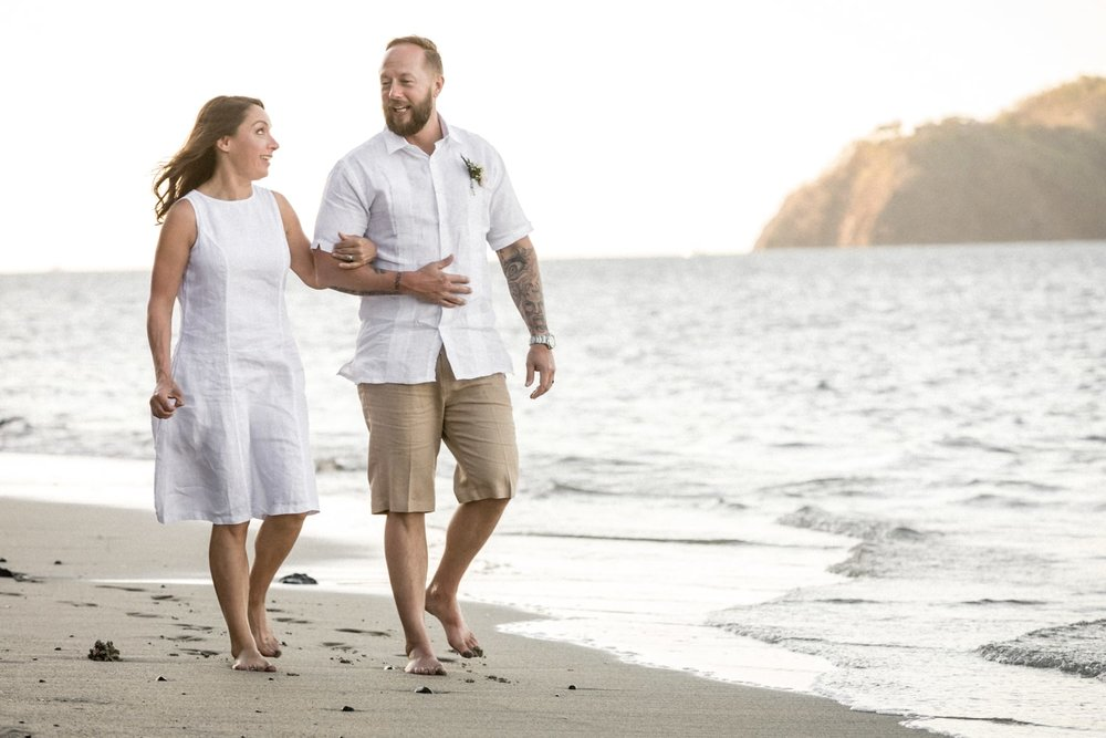 Bride and groom walking on gorgeous beach in Costa Rica.