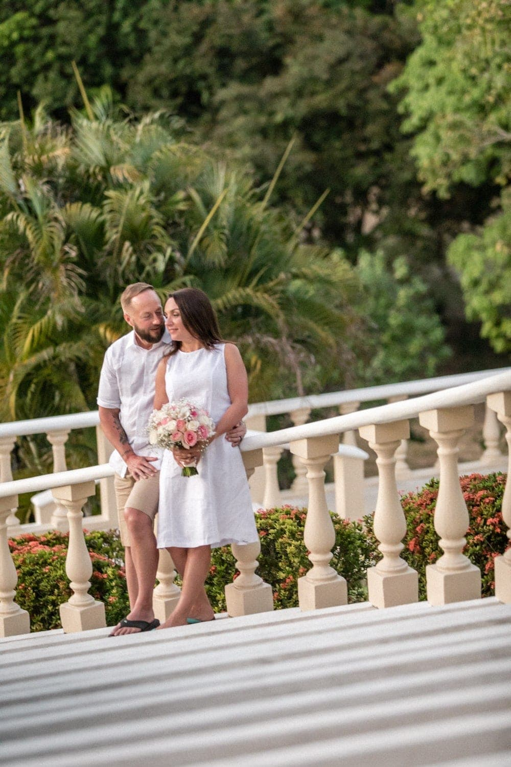 Just married couple poses for photo on staircase at sunset.
