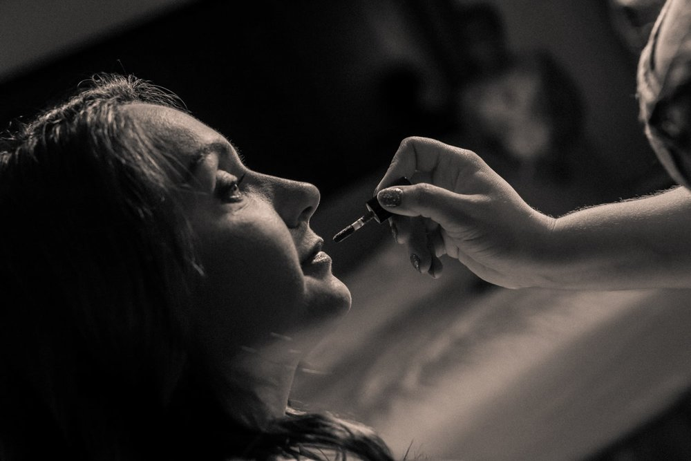 Black and white photo of bride having wedding day makeup done.