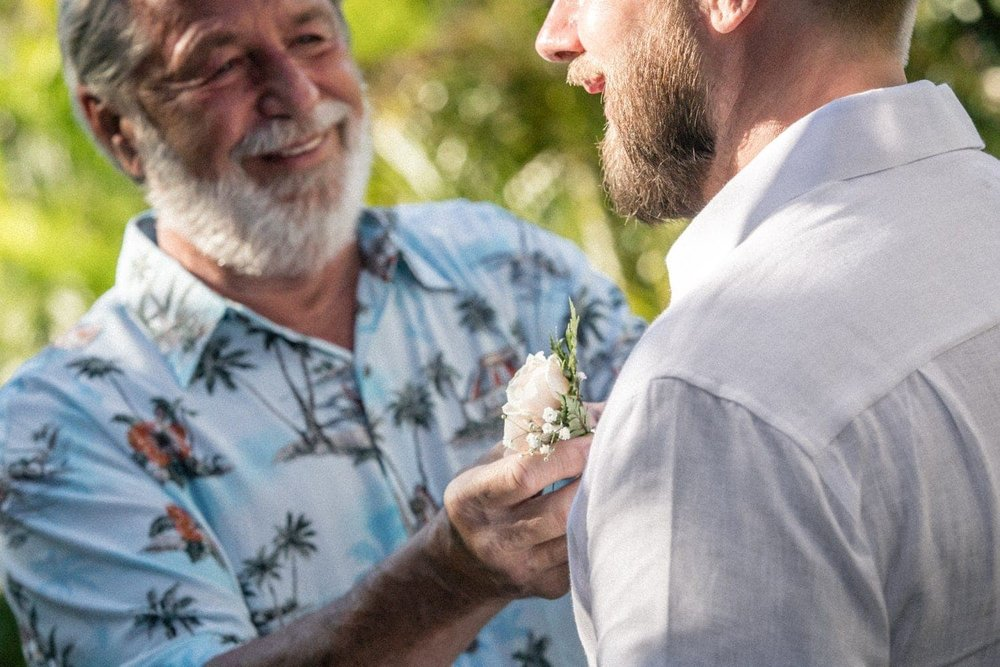 Groom's father pins boutonniere to his shirt on his wedding day.