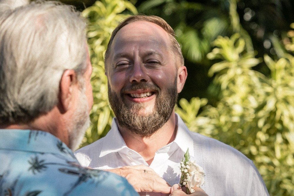 Father puts boutonniere on son before wedding ceremony.