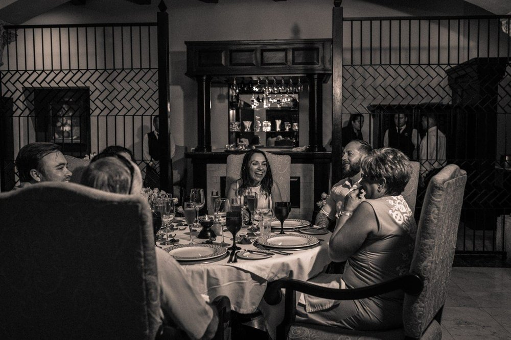 Black and white photo of bride and groom and family during wedding reception.