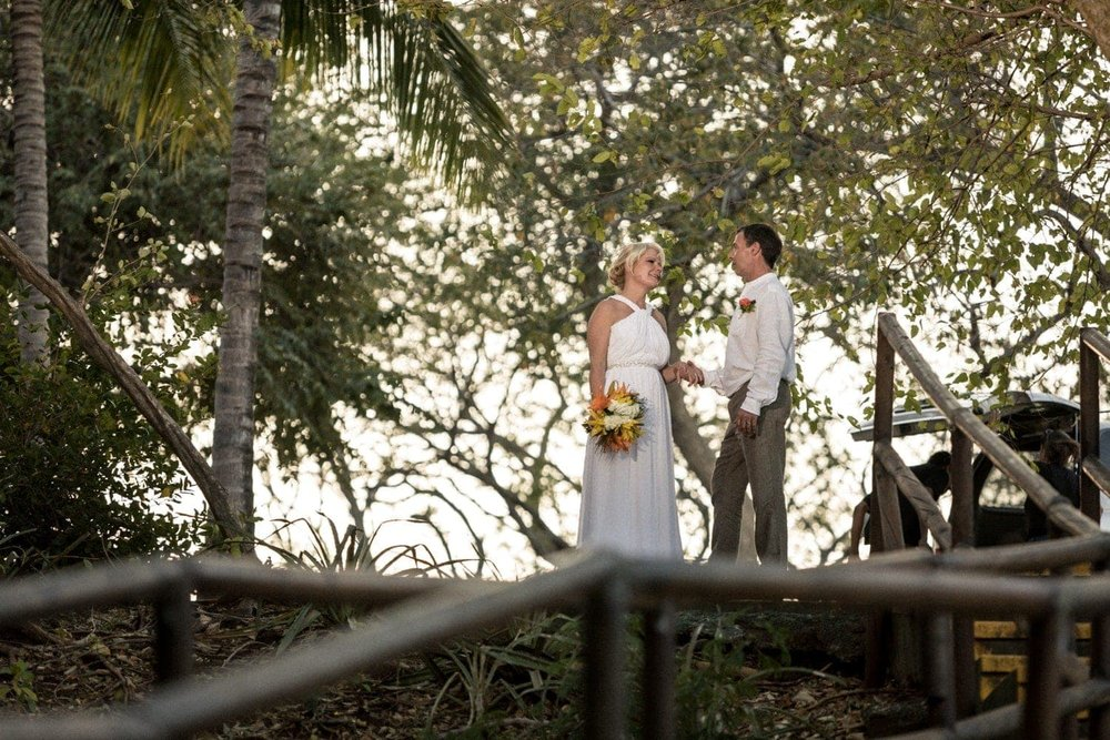Couple standing under trees after getting married at Occidental Papagayo Resort.
