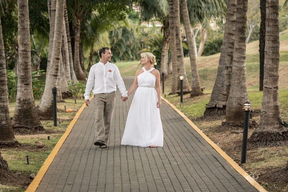 Bride and groom strolling down path lined with palm trees.