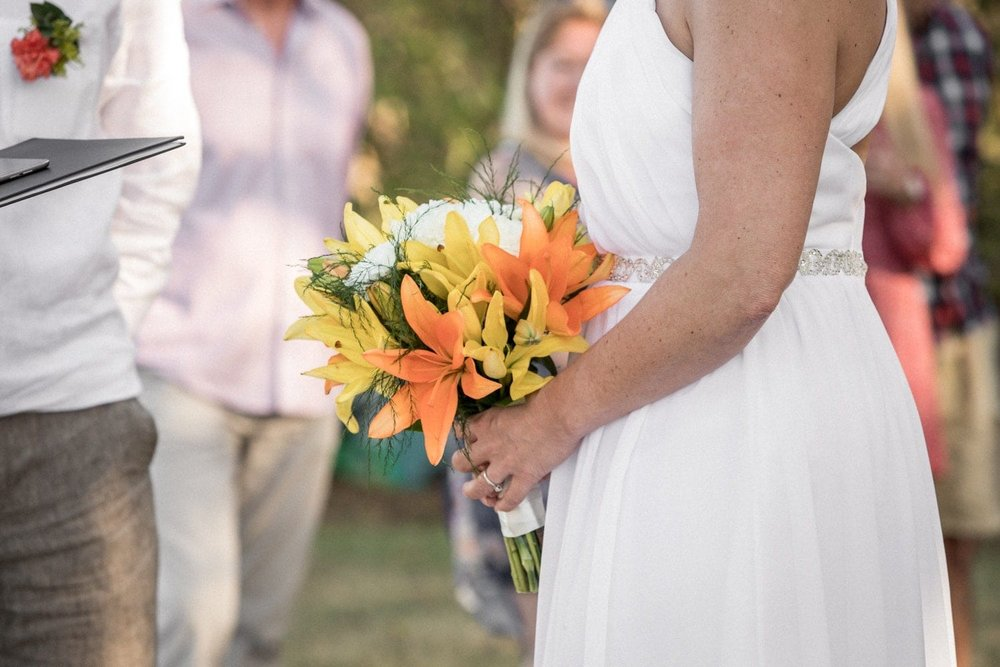 Bride holding tropical bouquet during wedding ceremony.