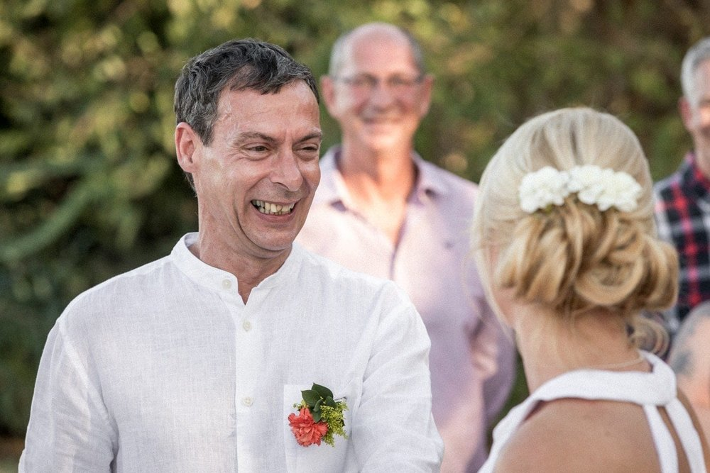 Groom smiles at bride when she reaches altar.