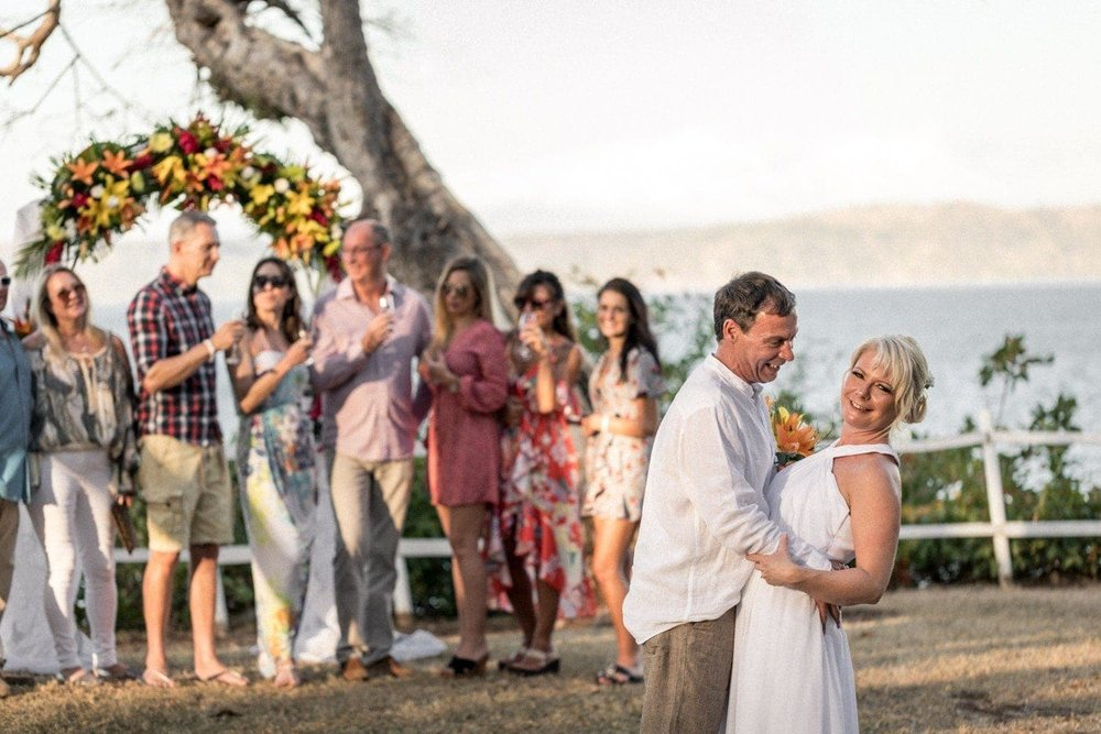 Romantic photo of just married couple with bridal party in background.