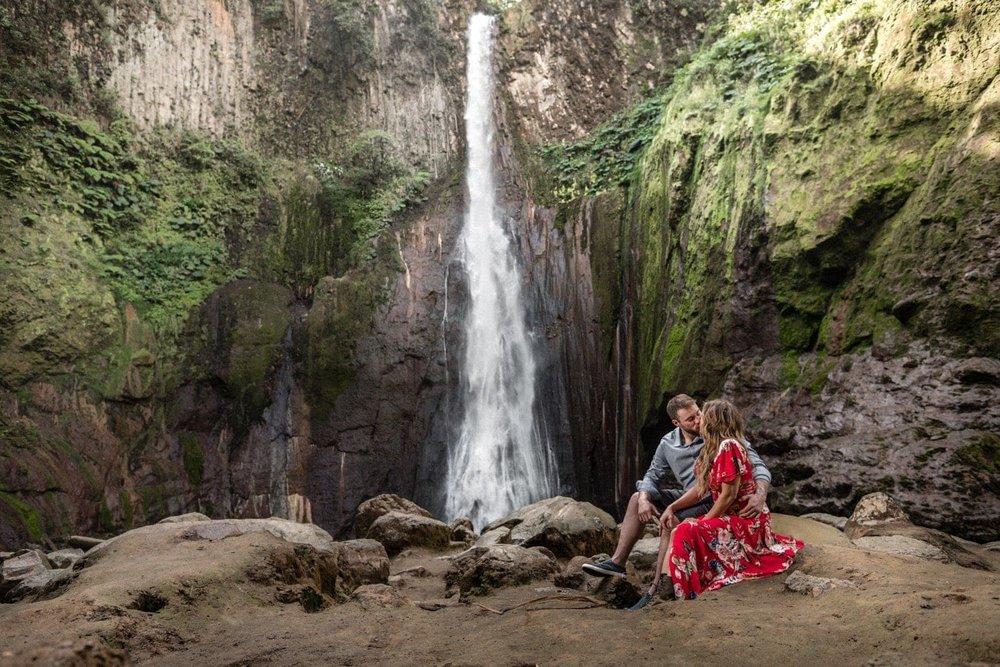 Just engaged couple sit near base of Catarata del Toro Waterfall, Costa Rica.