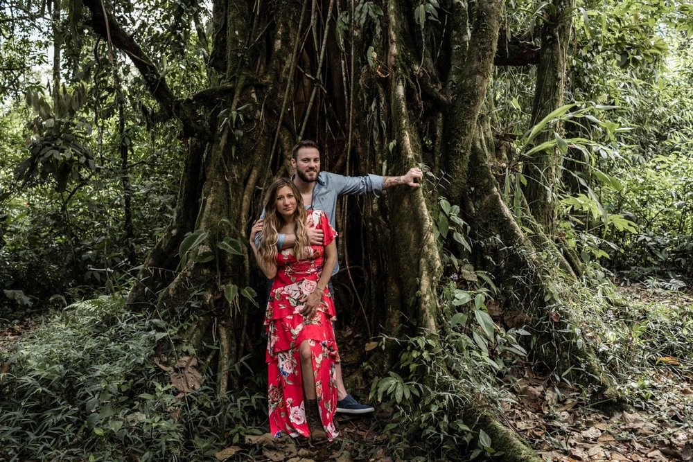 Couple in love pose in front of large tree in cloud forest.