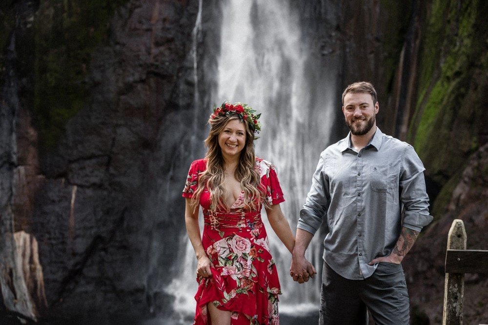 Couple in love standing in front of waterfall in Costa Rica.