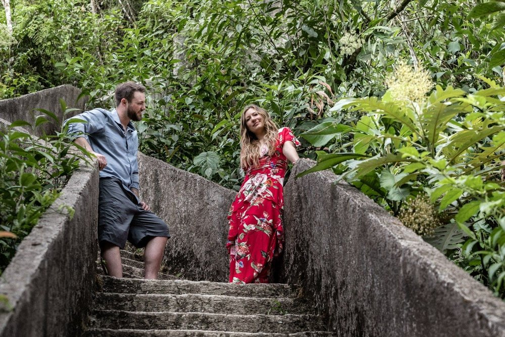 Woman wearing floral red dress looks at her fiancé.