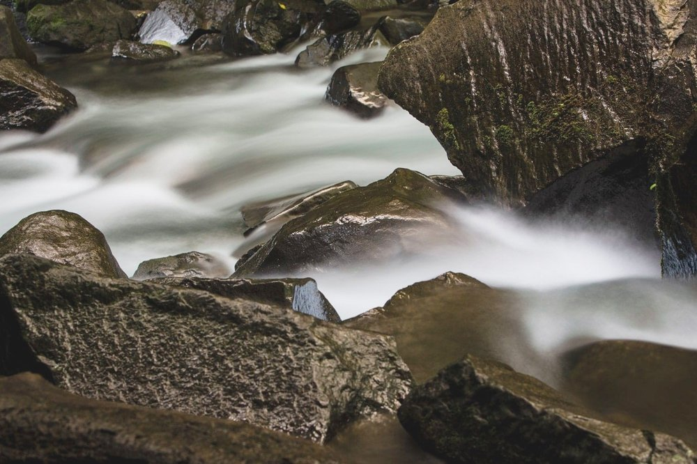 Long exposure photo of water flowing over large rocks coming from La Fortuna Waterfall.