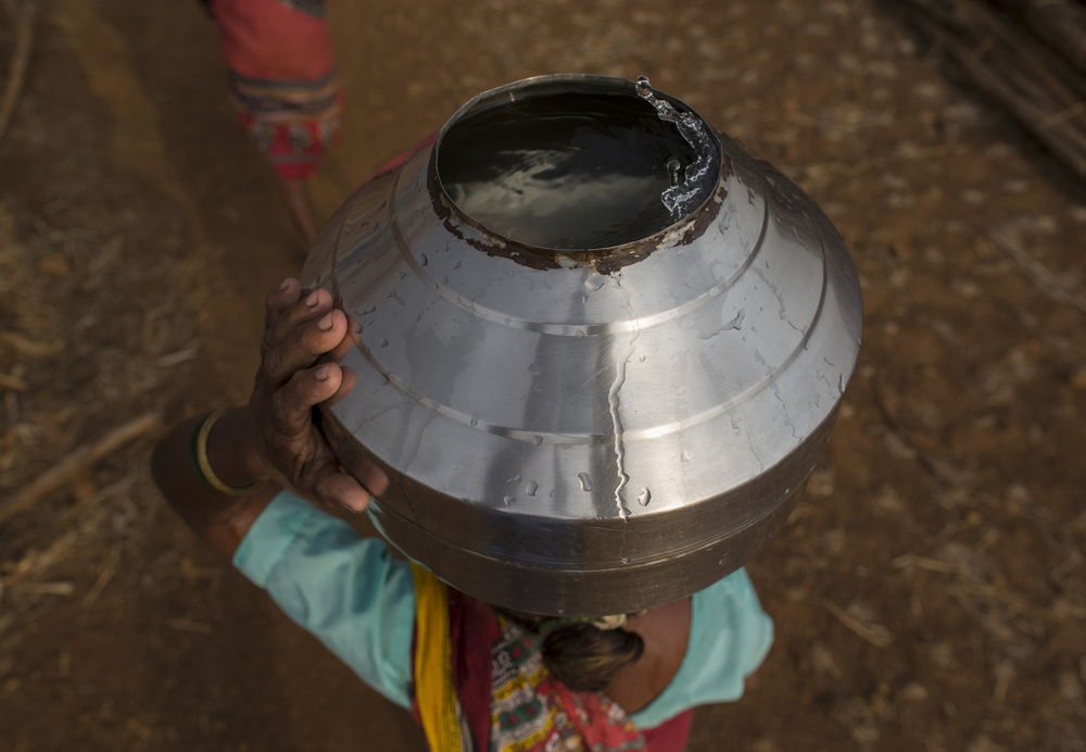 Bhaagi, third wife of Sakharam Bhagat, carries a metal pitcher filled with water from a well outside Denganmal village.