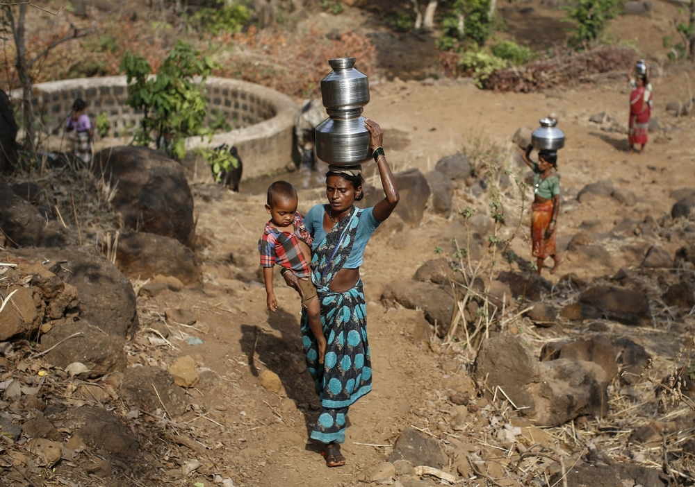 Shivarti, second wife of Namdeo, carries her grandson while carrying metal pitchers filled with water from a well outside Denganmal village.