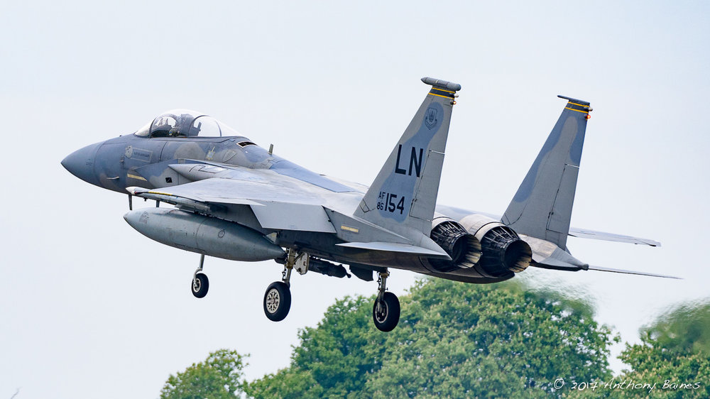 An F-15C Eagle goes over the perimeter fence at Lakenheath