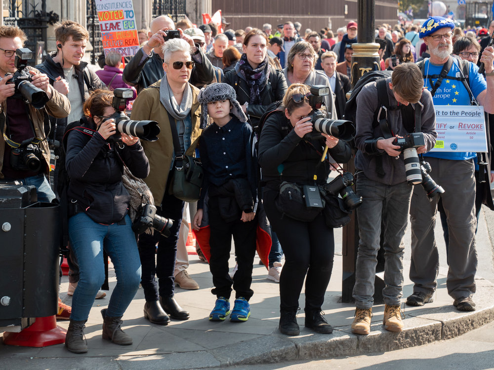 Whenever a ministerial car gingerly makes its way through the crowd (they certainly don't sweep in), photojournalists line up at the kerb to get pictures of the occupants. The flashes are to punch light through tinted windows. Meanwhile, everyone else waits to cross the road.