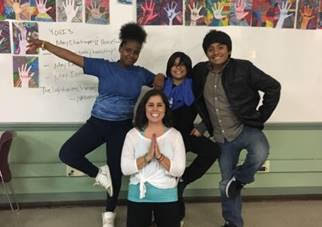 "Kayla with three of her students. They are practicing the ""tree pose,"" which requires standing on one leg. (Photos courtesy of Citizen Schools)"