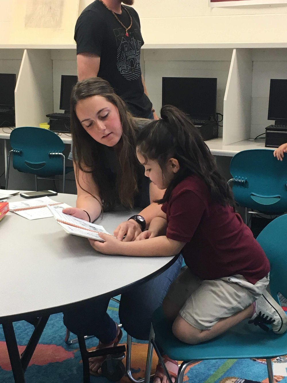 Karlee helping one of the kindergartners at the elementary school.