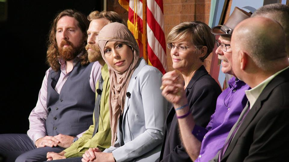 Regina listening to an opponent in a primary debate with other Rochester, MN mayoral candidates.